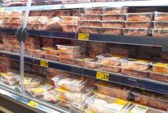 Koelkast met kippenvlees wordt gevuld voor verkoop in Duitse discountersupermarkt die stock foto