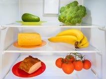 Koelkast met wat groen, geel en rood voedsel royalty-vrije stock foto's