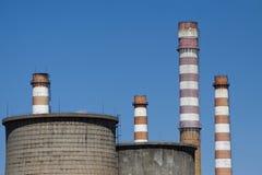 Koeltorens en industriële schoorstenen tegen blauwe hemel Stock Foto's