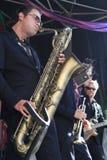 Koen Schouten juega el saxofón del barítono con los miembros de la banda Foto de archivo