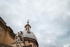 Koepel met engel op een barokke kerk in Rome met een bewolkte hemelbedelaars stock afbeelding