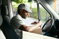 koerier De Lezingsadressen die van de leveringsmens in Leveringsbestelwagen zitten stock fotografie