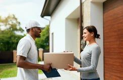Koerier Delivery Man die Pakket thuis leveren aan Vrouw stock foto