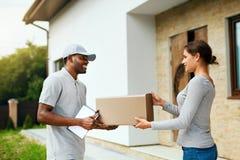 Koerier Delivery Man die Pakket thuis leveren aan Vrouw royalty-vrije stock afbeeldingen