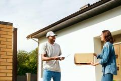Koerier Delivery Man die Pakket thuis leveren aan Vrouw royalty-vrije stock foto's