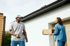 Koerier Delivery Man die Pakket thuis leveren aan Vrouw stock fotografie