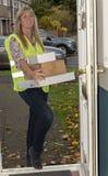 Koerier die bij voordeur een kartondoos leveren royalty-vrije stock afbeelding