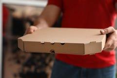 Koerier met pizzadoos op vage achtergrond, close-up stock foto