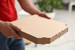 Koerier met pizzadoos op vage achtergrond, close-up royalty-vrije stock fotografie