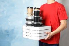 Koerier met stapel orden op kleurenachtergrond De dienst van de voedsellevering royalty-vrije stock foto's