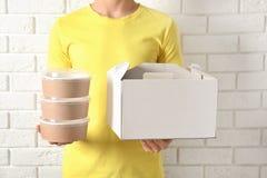 Koerier met verschillende containers dichtbij witte bakstenen muur, close-up stock afbeeldingen