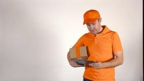 Koerier in oranje eenvormig leverend een pakket aan verkeerd adres Foutconcept, 4K studioschot stock footage