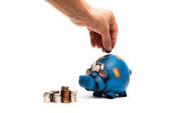Koespaarvarken met de close-up van de muntstukkenhand Stock Afbeelding