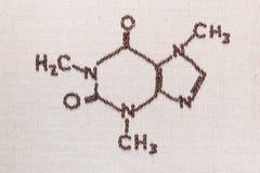 Koffeinformel från kaffebönor på lineatextur arkivfoto