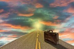 Koffer auf der Straße zum Himmel bei Sonnenuntergang Stockfoto