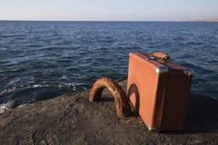 Koffer, der auf dem Strand steht Stockbild