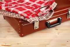 Koffer en kleren op houten achtergrond Stock Fotografie