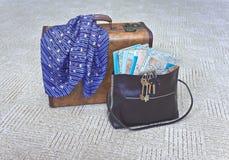 Koffer und Handtasche sind auf dem Teppich. Lizenzfreie Stockbilder