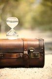 Koffer und Sanduhr mit Unschärfehintergrund Lizenzfreies Stockfoto