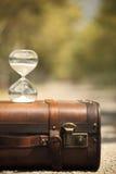 Koffer und Sanduhr mit Unschärfehintergrund Lizenzfreie Stockfotografie