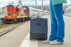 Koffer und weibliche Füße, die auf einen Zug warten Stockbilder