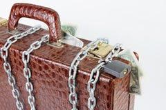 Koffer voll Geld wird mit einem verschlossenen Vorhängeschloß angekettet Lizenzfreies Stockbild