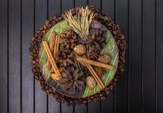 Koffie, anijsplant, kaneel en notemuskaat in houten kom op houten achtergrond Stock Foto's