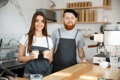 Koffie Bedrijfsconcept - de Positieve jonge gebaarde mens en het mooie aantrekkelijke het paar van damebarista geven halen kop we Royalty-vrije Stock Fotografie