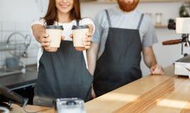 Koffie Bedrijfsconcept - de Positieve jonge gebaarde mens en het mooie aantrekkelijke het paar van damebarista geven halen kop we Stock Fotografie