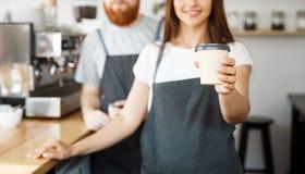 Koffie Bedrijfsconcept - de Positieve jonge gebaarde mens en het mooie aantrekkelijke het paar van damebarista geven halen kop we royalty-vrije stock foto's