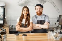 Koffie Bedrijfsconcept - de Positieve jonge gebaarde mens en mooie aantrekkelijke damebarista koppelen in schort bekijkend stock fotografie