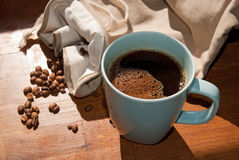 Koffie in blauwe mok en droogtekoffiebonen in zonneschijn Royalty-vrije Stock Afbeelding