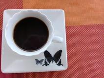 Koffie bovenop een schotel met vlinderontwerp royalty-vrije stock foto