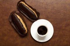 Koffie, chocolade Eclair, koffie in een witte Kop, witte schotel, op een bruine lijst, Eclair aangaande document tribune stock foto