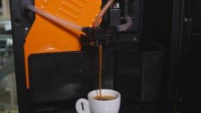 Koffie die over de randen van de kop van de koffiemachine wordt gegoten stock footage