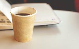 Koffie in een rekupereerbaar document beschikbaar glas met een open notitieboekje op achtergrond royalty-vrije stock afbeelding