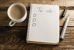 Koffie en agenda notepads Een nota Aan-maken van een lijst Stock Foto