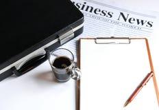 Koffie en aktentas met notitieboekje op newpaper royalty-vrije stock afbeeldingen