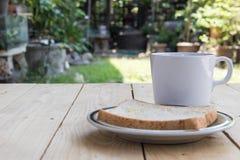 Koffie en brood op houten lijst Stock Afbeeldingen