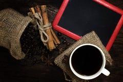Koffie en koffiebonen en pijpjes kaneel met en kentekens op houten lijst Royalty-vrije Stock Afbeeldingen