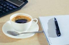 Koffie en notitieboekje op het bureau Stock Foto's