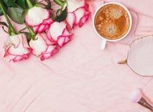 Koffie en rozen op de roze doekachtergrond stock afbeelding