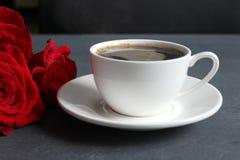 Koffie en rozen, stilleven Zwarte koffie in een witte Kop met een schotel op de lijst, een boeket van rode rozen stock afbeeldingen