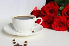 Koffie en rozen, stilleven Zwarte koffie in een witte Kop met een schotel op de lijst, een boeket van rode rozen royalty-vrije stock afbeeldingen
