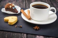 Koffie en snoepjes op een houten lijst stock foto