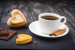 Koffie en snoepjes op een houten lijst stock foto's
