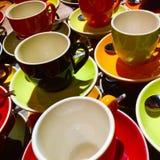 Koffie en theekopjes in kleurensinaasappel, geel, rood en zwart stock afbeelding