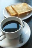 Koffie en toost op houten lijst Royalty-vrije Stock Foto's