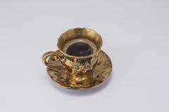 Koffie in gouden kop Stock Afbeeldingen