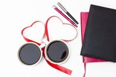 Koffie, harten van rood lint, roze en zwarte agenda's met pennen op een witte achtergrond Royalty-vrije Stock Fotografie